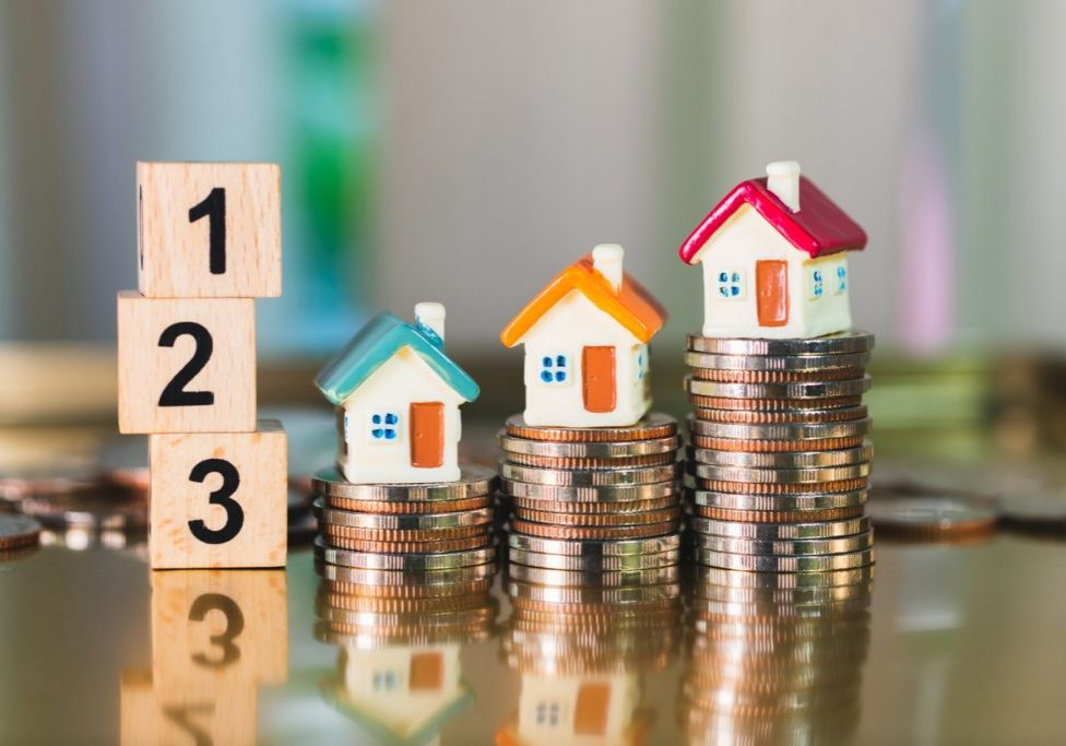Miniature colorful house on stack coins with wooden block number using as property and financial concept