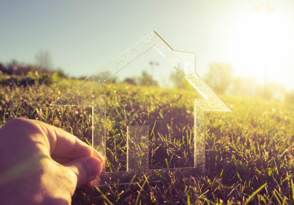 Hand holding transparent house symbol in green field against the sun